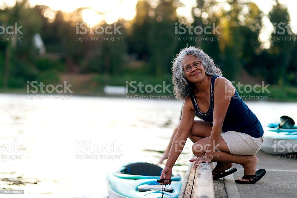 Elderly woman ready to kayak stock photo