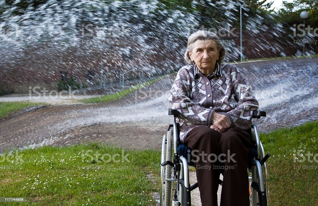Elderly Woman Relaxing by the Fountain in a Park stock photo