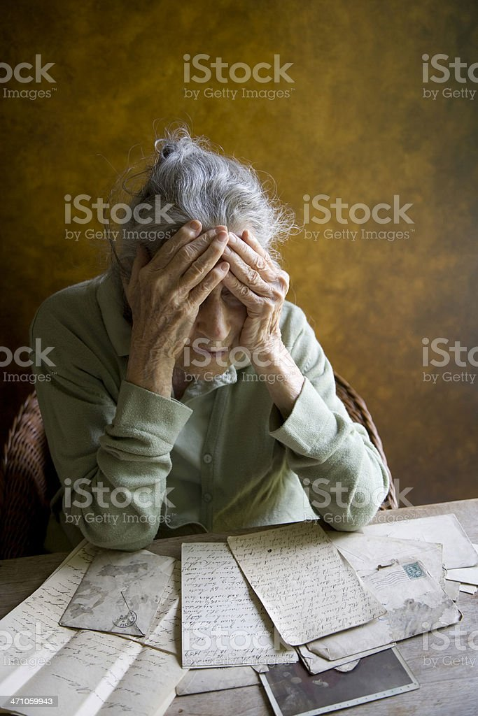 Elderly woman reminiscing over old letters and photos stock photo