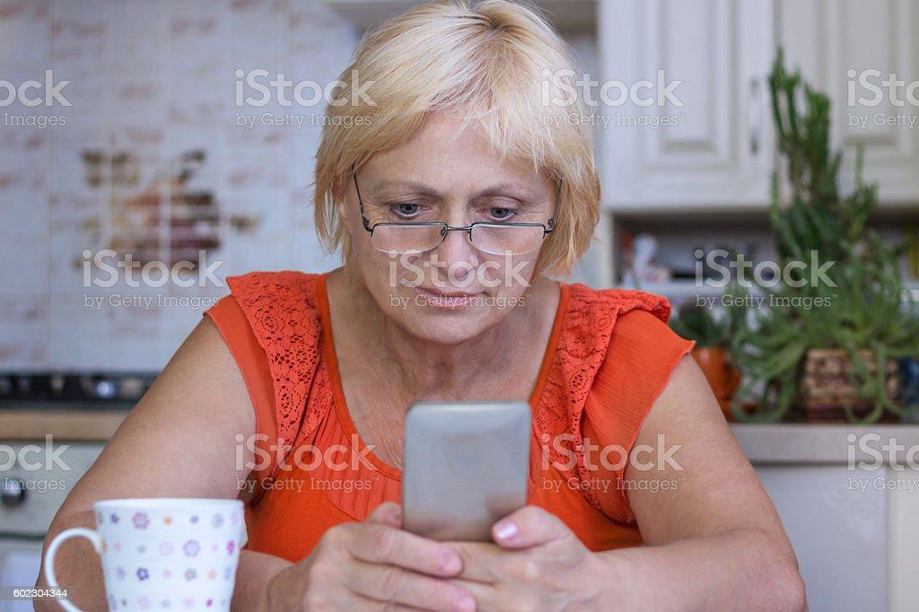 Elderly woman sends sms on cellar phone stock photo