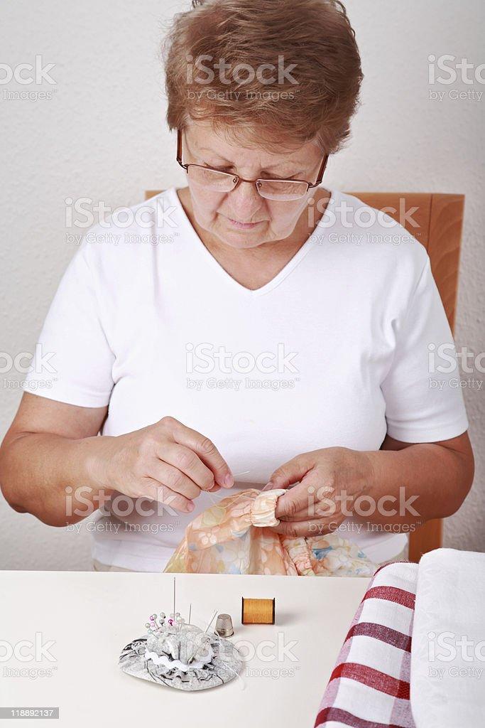 Elderly woman sewing stock photo