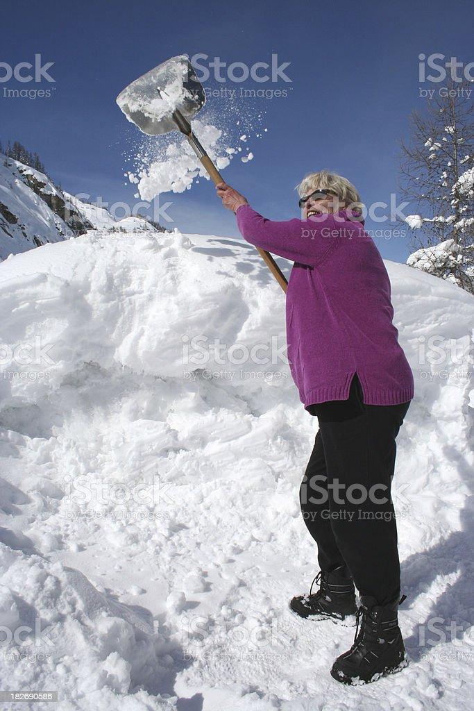 Elderly woman shoveling snow royalty-free stock photo