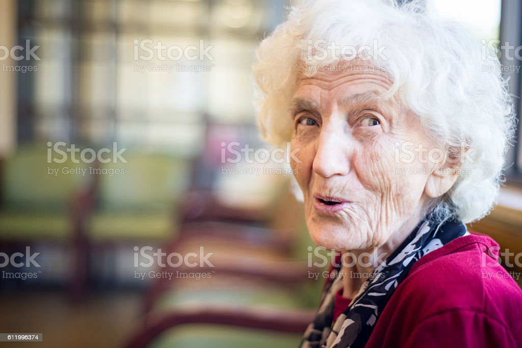 Elderly woman sitting in waiting room at doctor office stock photo