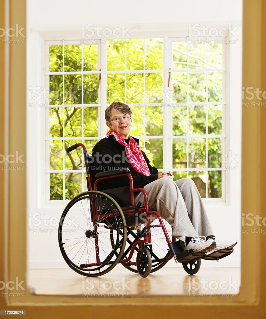 Elderly woman sitting in wheelchair, framed by doorway, smiles gently royalty-free stock photo