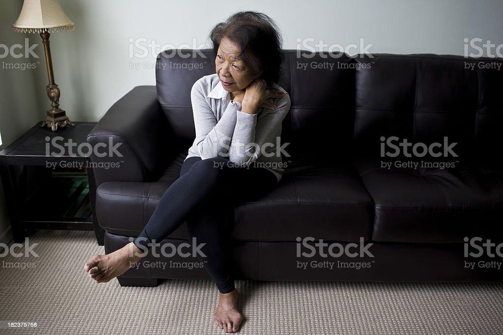 Elderly Woman sitting on her sofa royalty-free stock photo