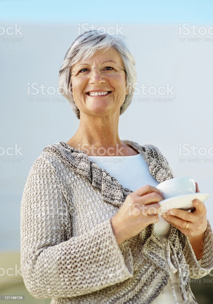 Elderly woman smiling with a cup of coffee royalty-free stock photo
