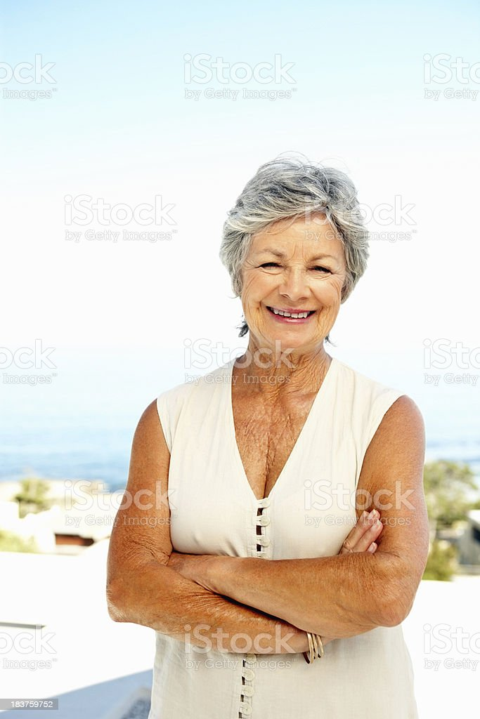 Elderly woman smiling with arms folded royalty-free stock photo