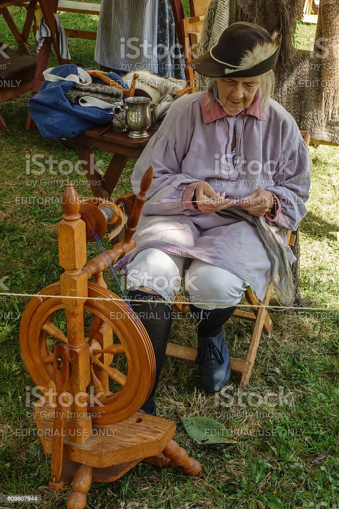 Elderly woman spinning yarn in mock military encampment stock photo