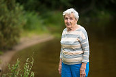 Elderly woman stands in the Park near the pond.