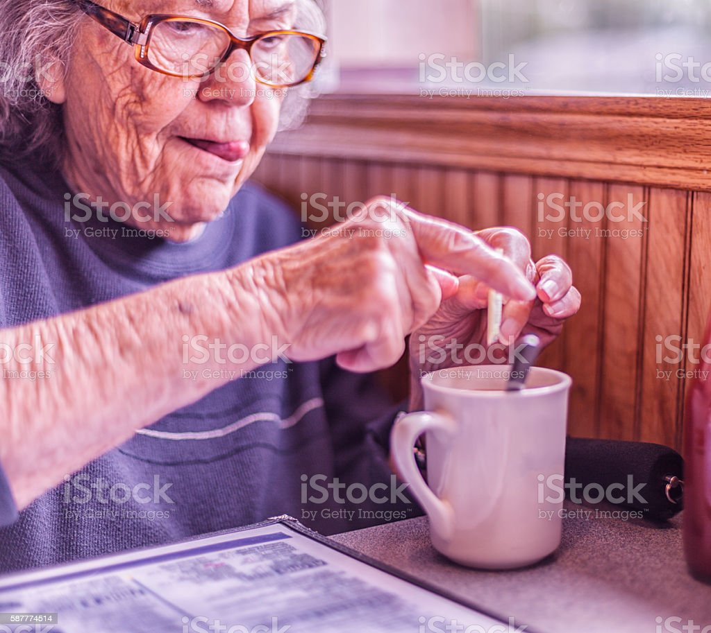 Elderly Woman Sticking Tongue Out Concentration Funny Face stock photo