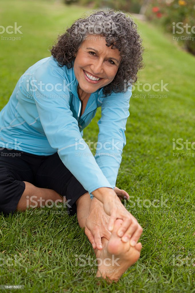 Elderly woman stretching outside royalty-free stock photo