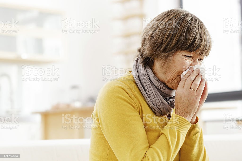 Elderly woman suffers from a cold royalty-free stock photo