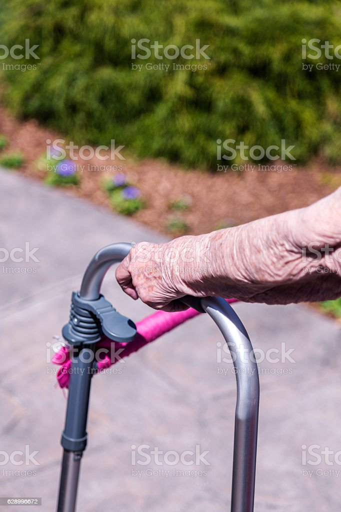 Elderly Woman Taking a Walk Gripping Orthopedic Walker Close-Up stock photo