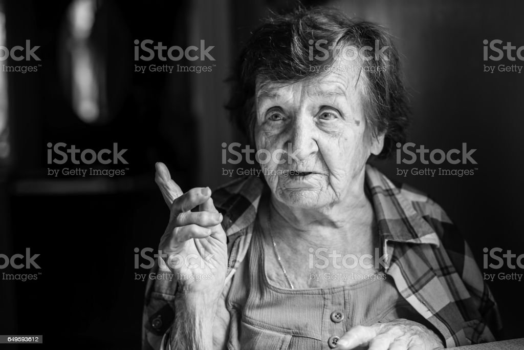 Elderly woman talking sitting at the table. Black-and-white photo. stock photo