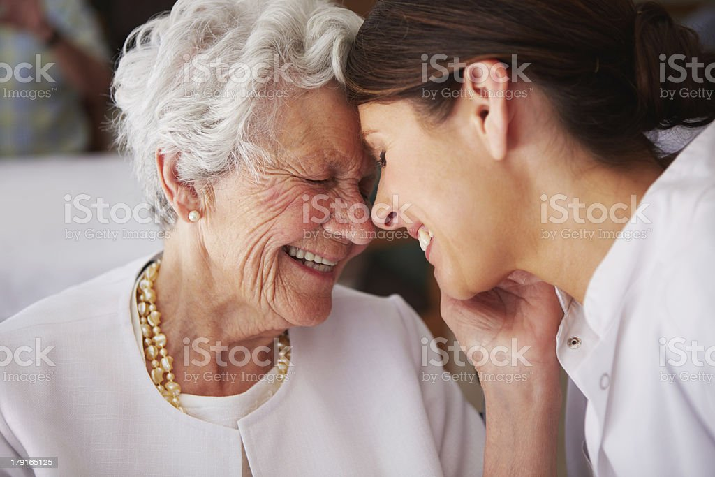 Elderly woman touching face of young female nurse stock photo