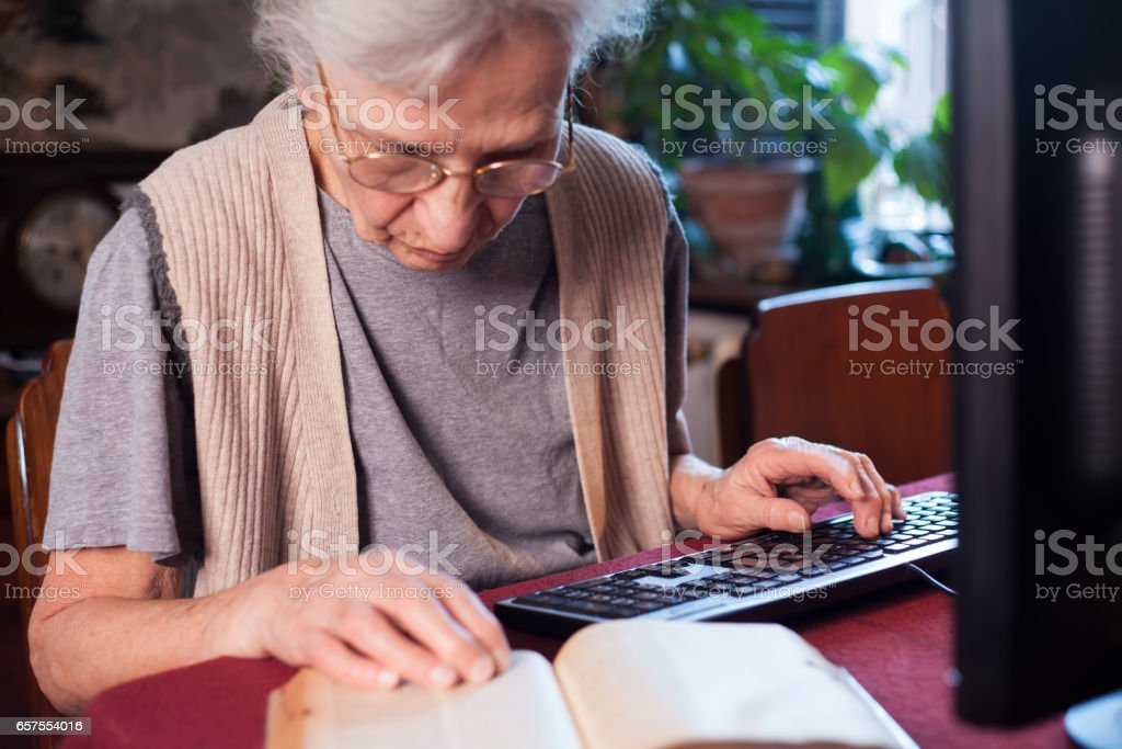 elderly woman translating a book stock photo