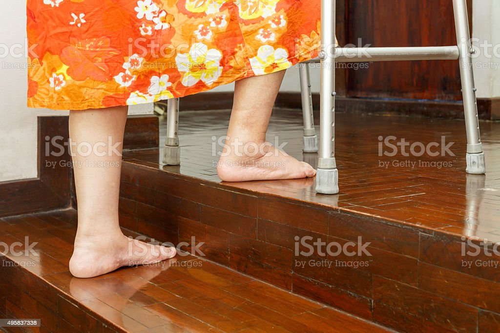 Elderly woman up stairs with walker at home. stock photo