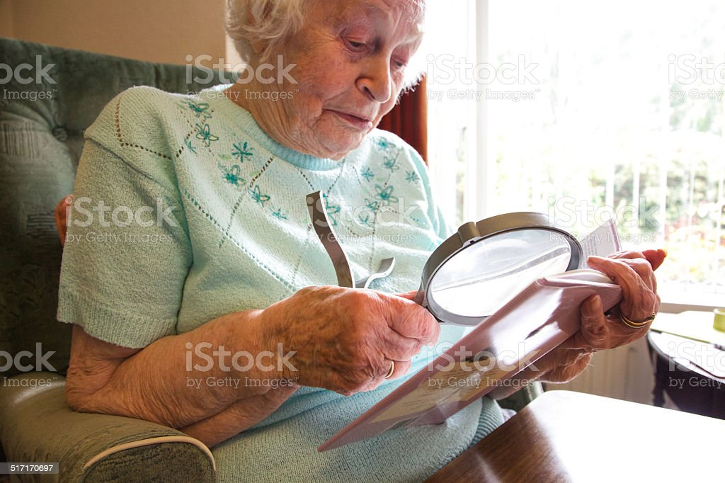 Elderly woman using a magnifier to read a book stock photo
