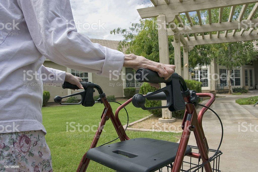 Elderly woman using a walker outdoors stock photo