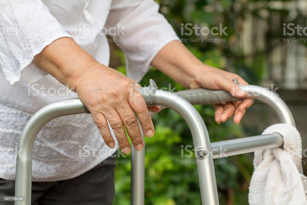 Elderly woman using a walker stock photo