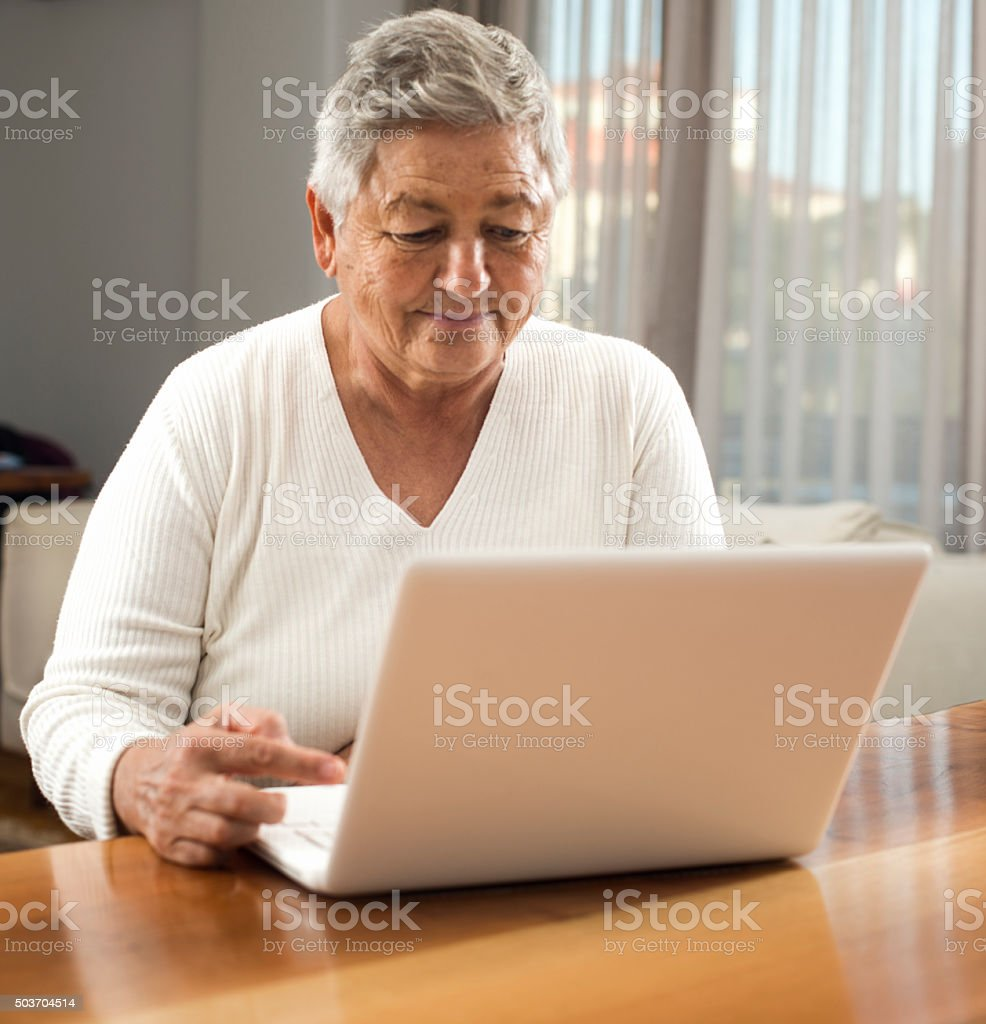 Elderly woman using laptop stock photo