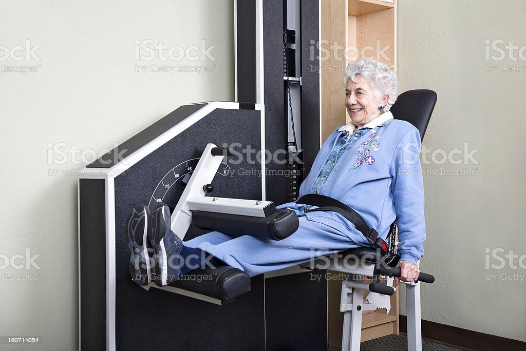 Elderly Woman Using Leg Weight Machine stock photo