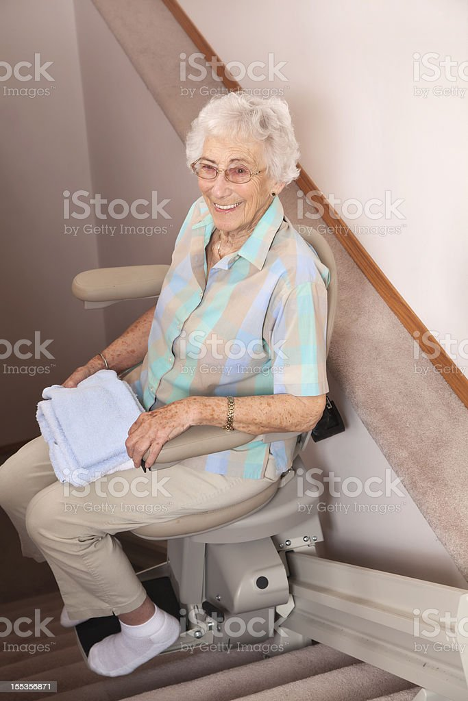 Elderly woman using stairlift: assisted living royalty-free stock photo