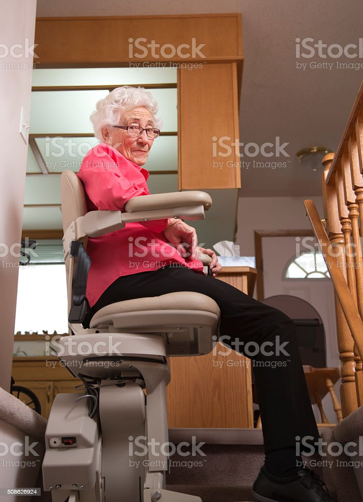 Elderly woman using stairlift: assisted living stock photo