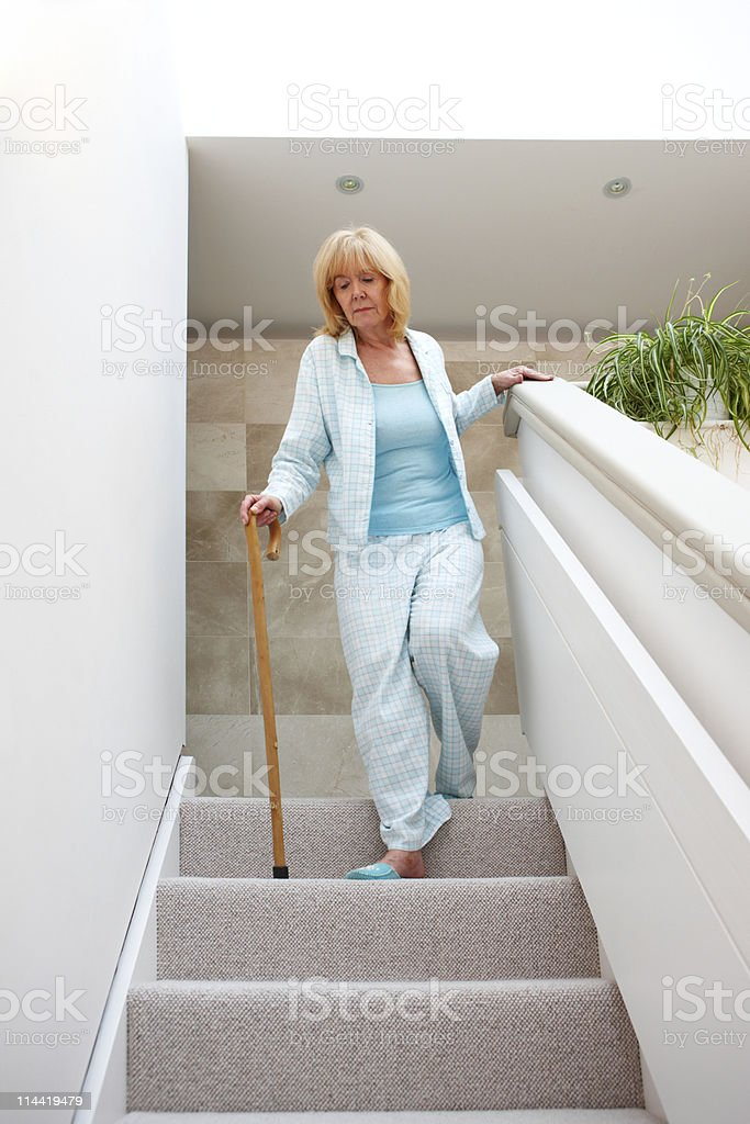 Elderly Woman Walking Down Stairs royalty-free stock photo
