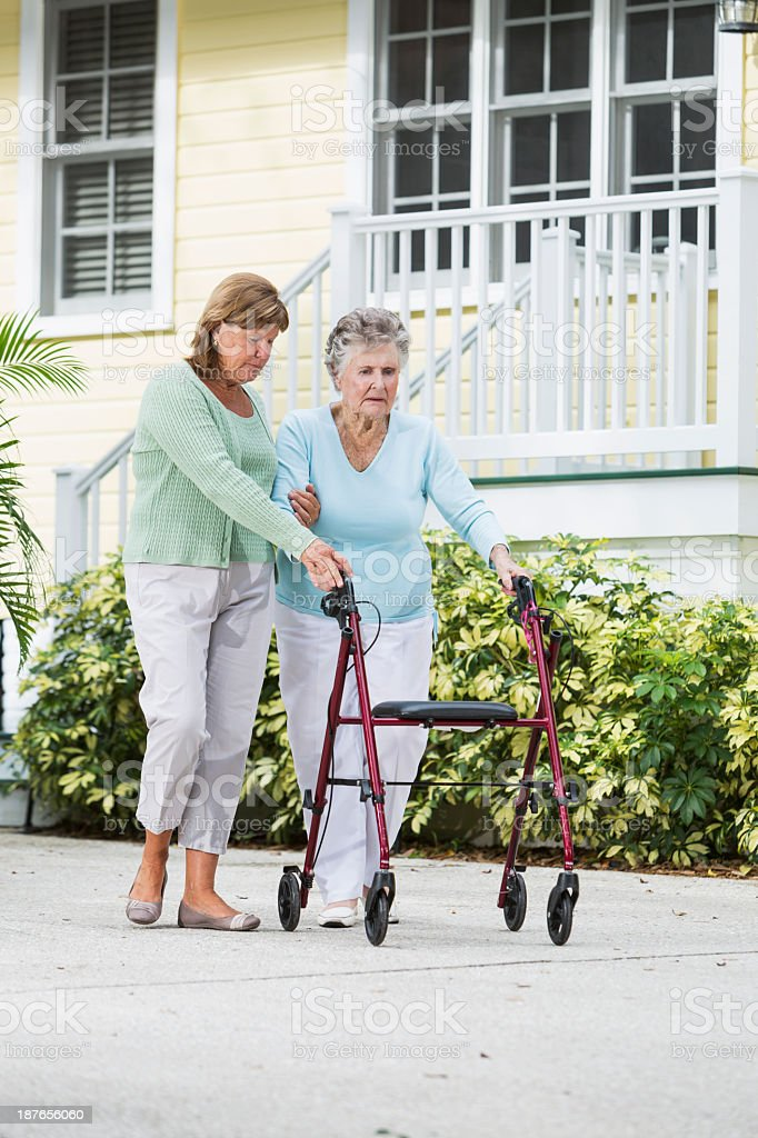 Elderly woman walking with adult daughter royalty-free stock photo