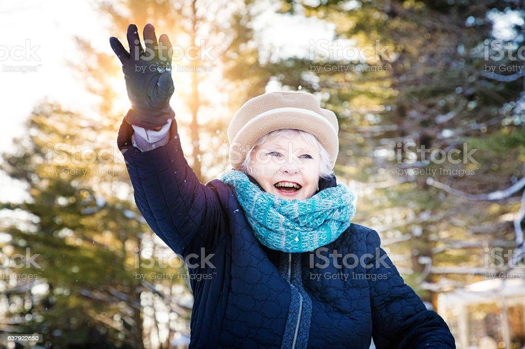 Elderly woman waves to grand children smiling Winter scene stock photo