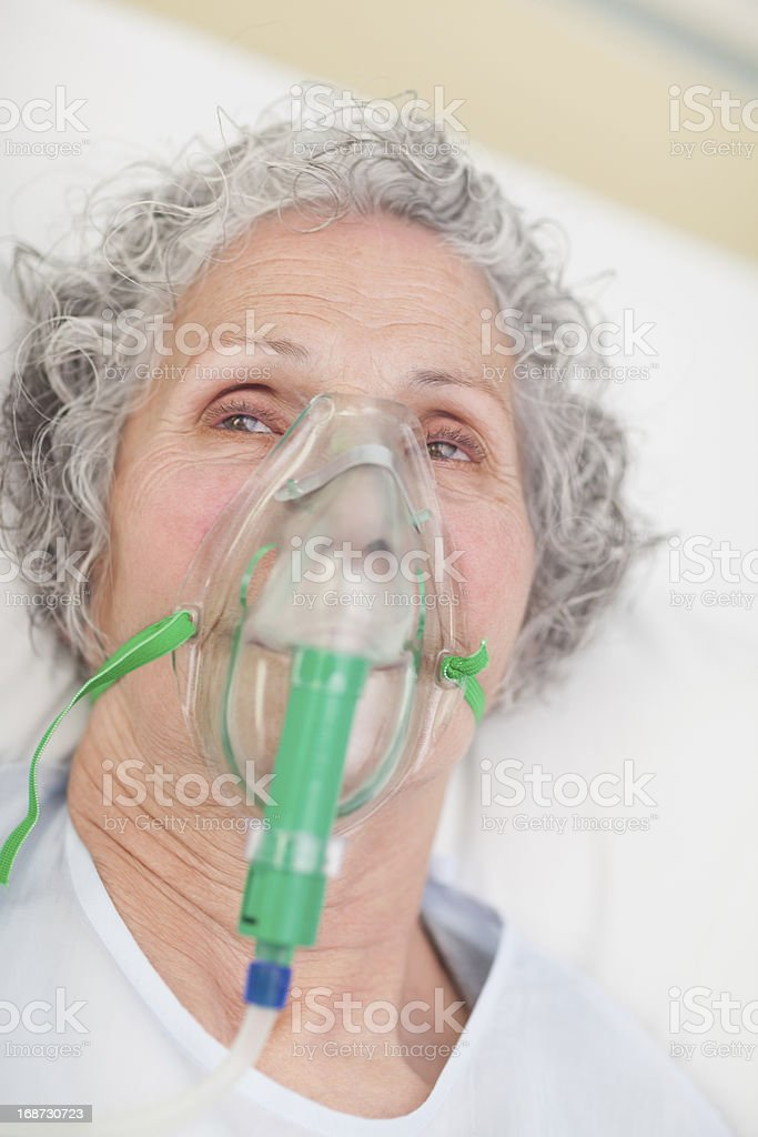 Elderly woman with an oxygen mask in a hospital royalty-free stock photo