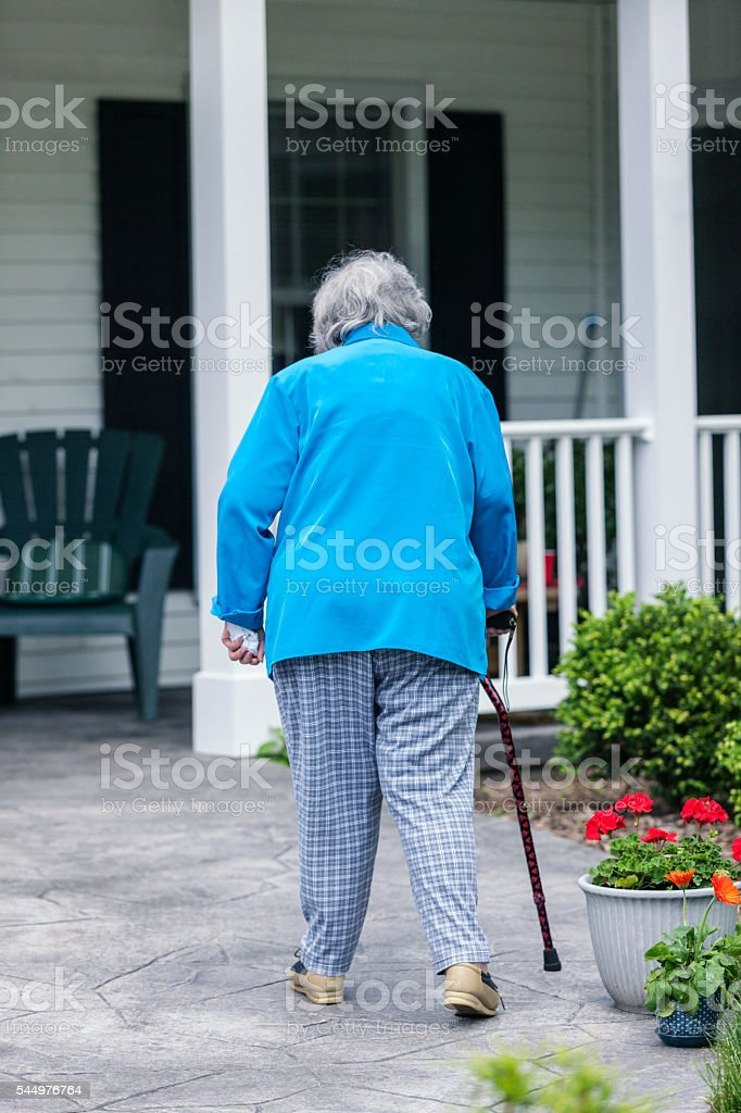 Elderly Woman With Cane Walking Up Ramp To Home Porch stock photo