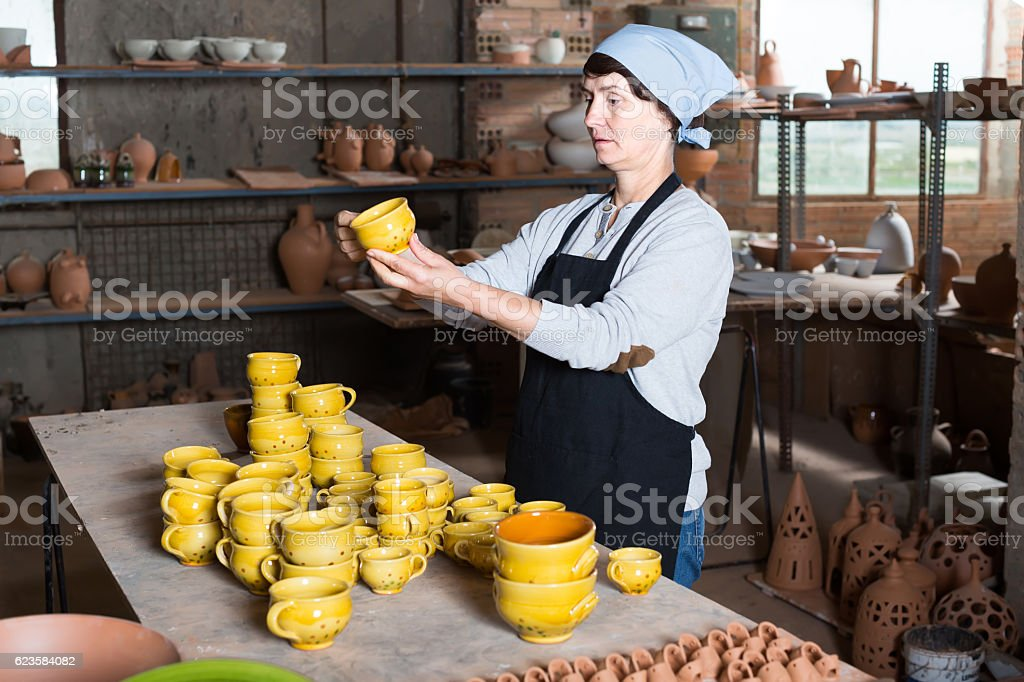 elderly woman with cups at pottery workshop stock photo
