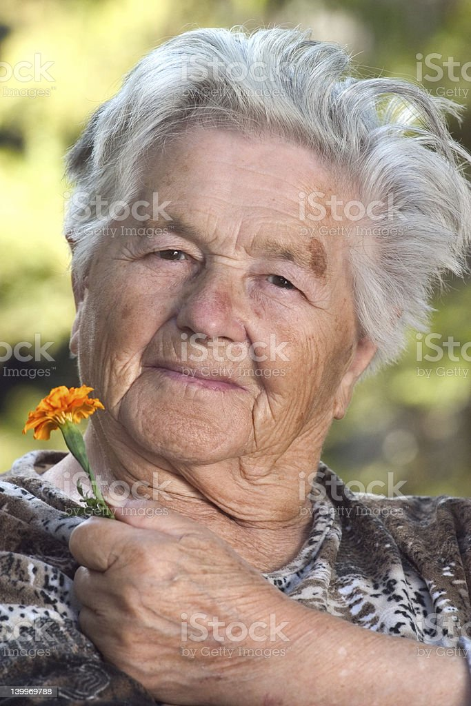 Elderly woman with flower royalty-free stock photo