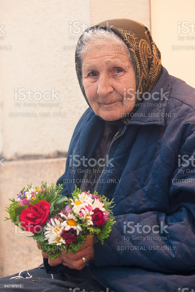 Elderly woman with flowers stock photo