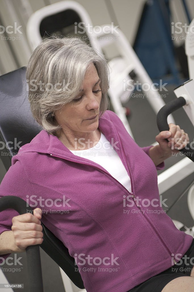 Elderly woman working out in pink jacket royalty-free stock photo