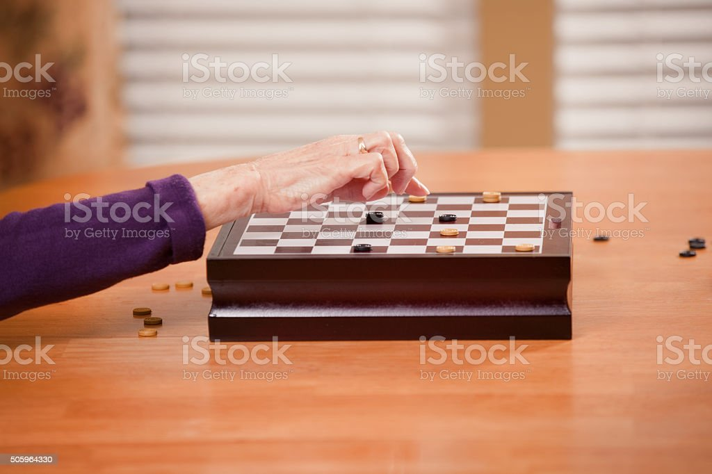 Elderly Woman's Hand Moving Checker on Game Board stock photo