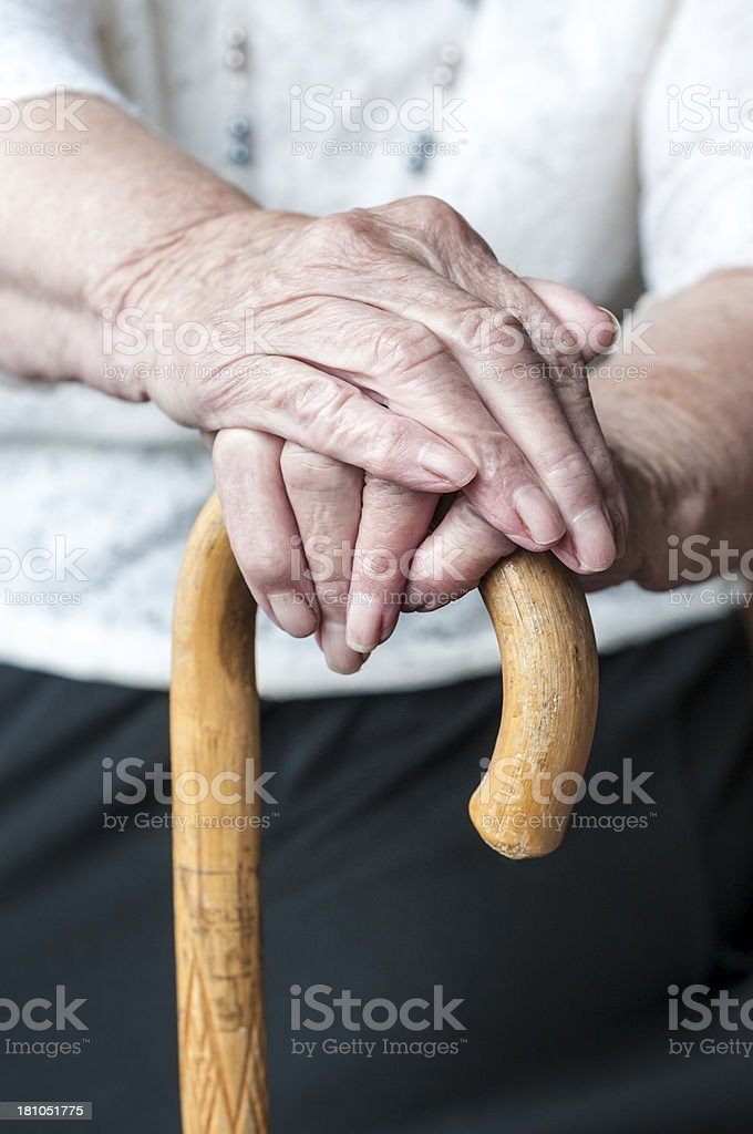 Elderly Woman's Hands Holding A Walking Cane stock photo