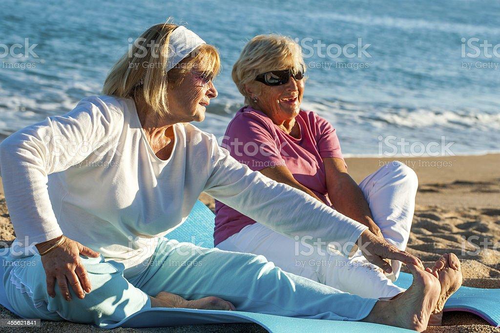 Femmes âgées faisant des étirements exerce sur la plage. photo libre de droits