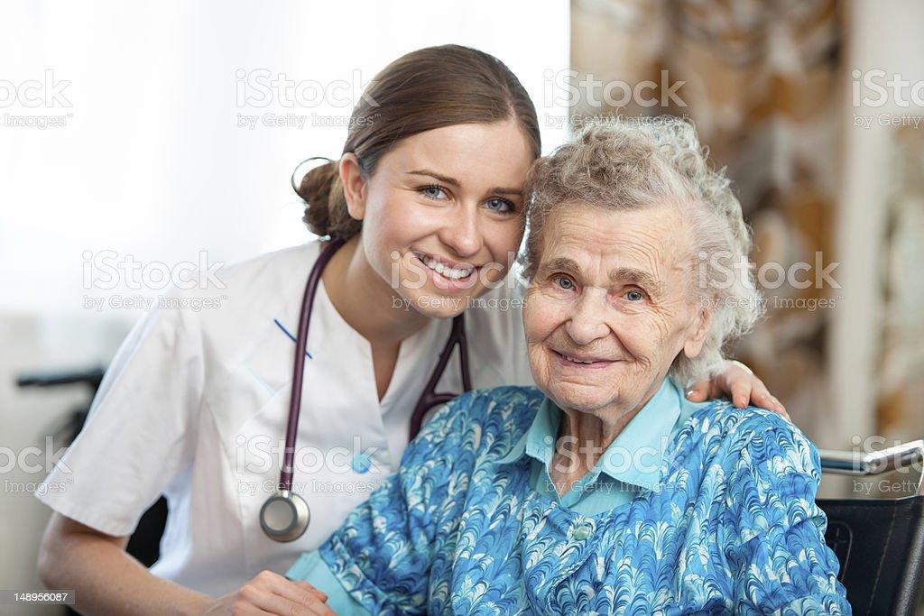 Elderly women posing with a nurse stock photo