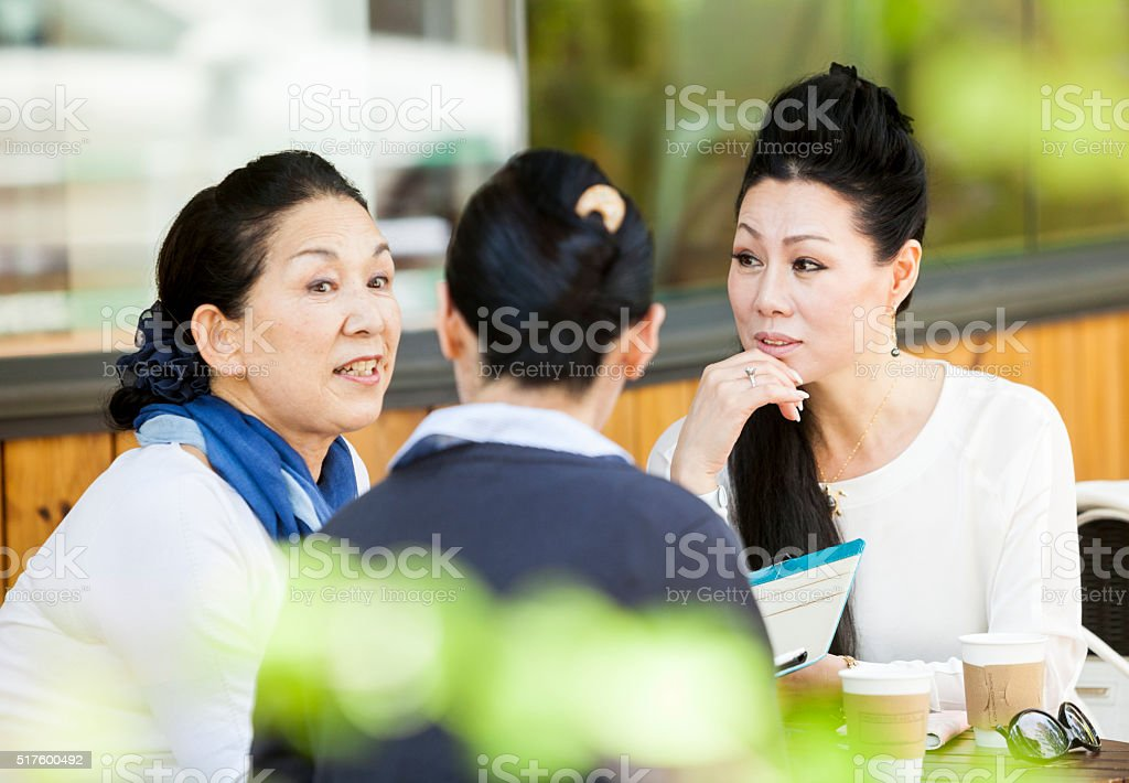 Elderly Women Sharing Thoughts In An Outdoors Cafe stock photo