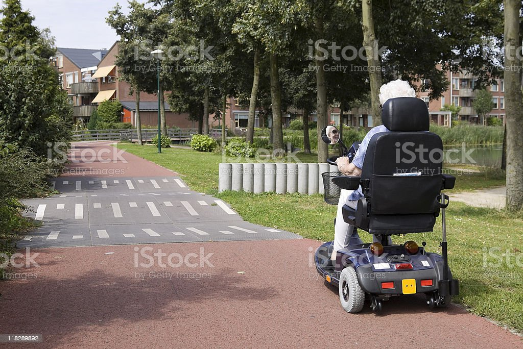 eldery woman on electric scooter stock photo