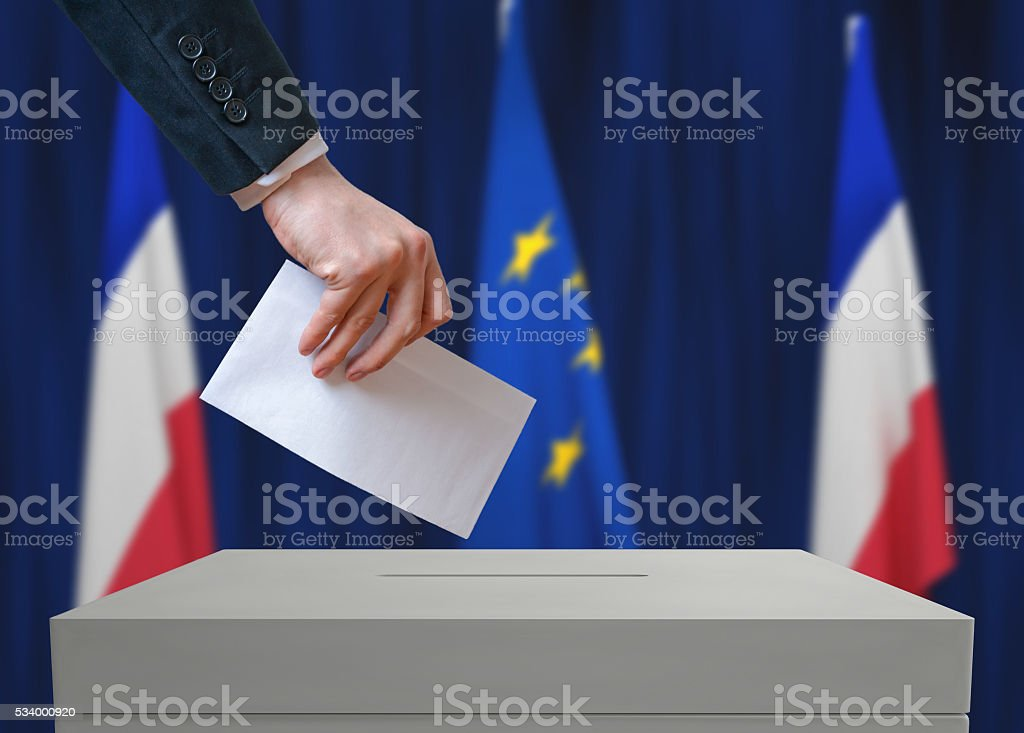 Election in France. Voter holds envelope above vote ballot. stock photo