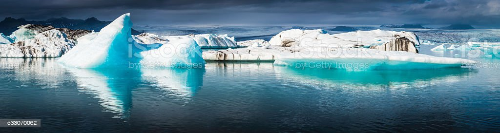 Electric blue icebergs floating in Arctic Ocean lagoon panorama Iceland stock photo