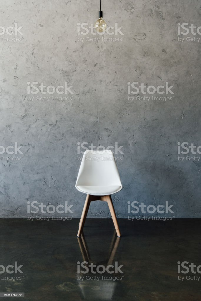 electric bulb and modern white chair on the floor at empty room stock photo