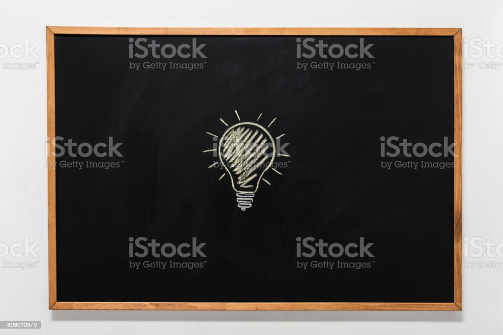 electric bulb drawn on black chalkboard in wooden frame stock photo