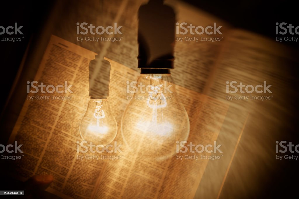 electric bulb illuminating a book stock photo