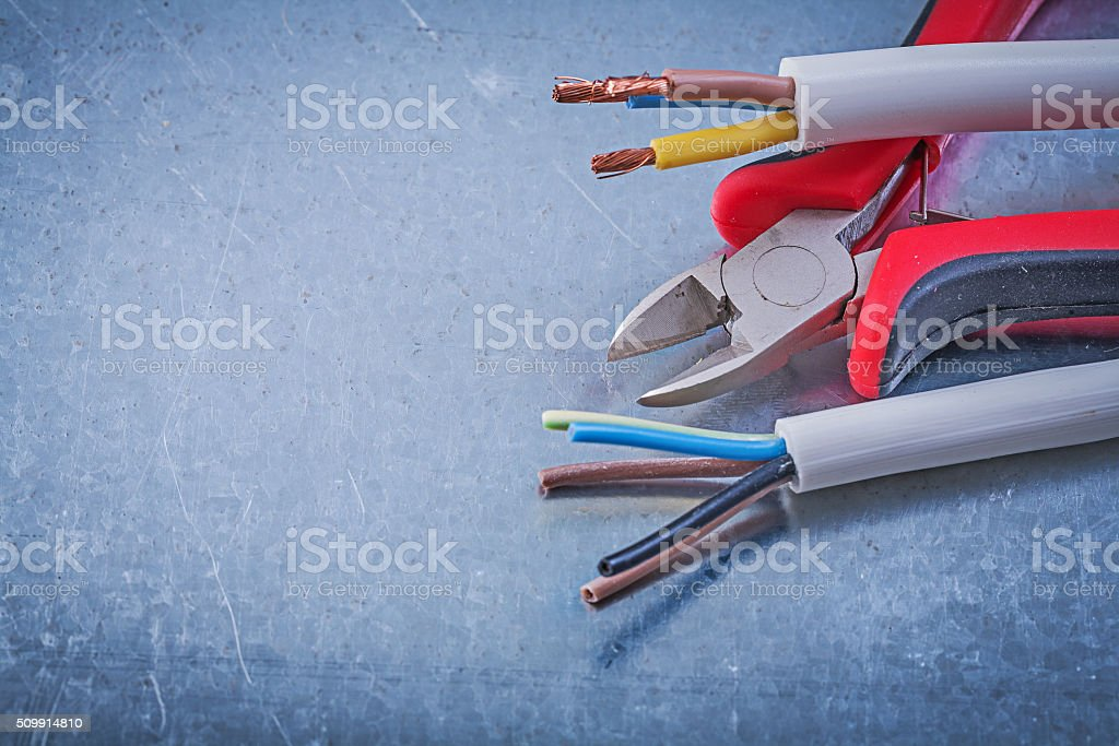 Electric cables wires nippers on scratched metallic background c stock photo