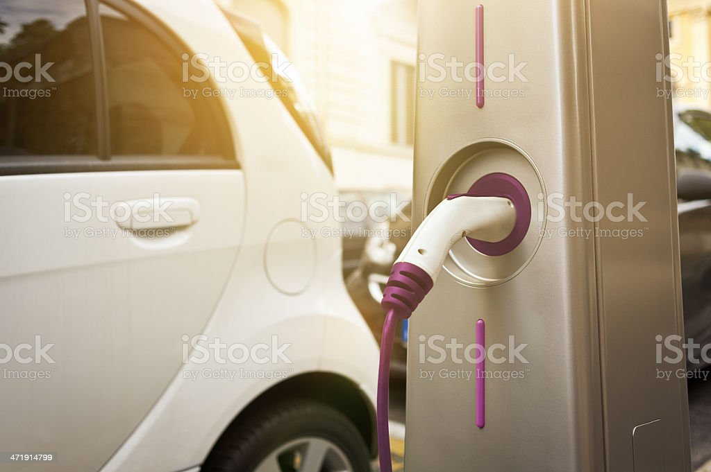 Electric car being charged at a charging station stock photo
